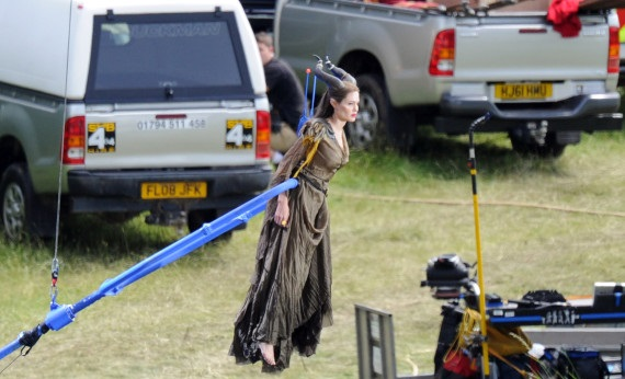 Angelina Jolie is hoisted into the air by a crane as she shoots scenes from the new Disney movie, 'Maleficent'. The 37-year-old actress, who is shooting the new movie in Buckinghamshire, England, stars as the title character - the evil Maleficent - in the film, a real-life version of the Disney cartoon Sleeping Beauty. Wearing her horned headdress, complete with prosthetic cheekbones and a long brown dress and matching cape, Jolie looked calm and confident as she was lifted up into the air by the crane, which was attached to her around the waist.Pictured: Angelina JolieRef: SPL410662  260612  Picture by: Almasi / Greg Sirc / Splash NewsSplash News and PicturesLos Angeles:	310-821-2666New York:	212-619-2666London:	870-934-2666photodesk@splashnews.com